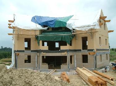 Das strohballengedämmte Dach ist bereits montiert, im Erdgeschoß sieht man die bereits montierten (magnesitgebundenen) Heraklith-Platten als Putzträger.