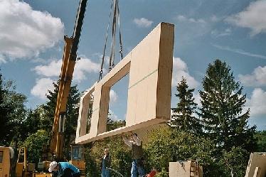 Mit dem Kran werden die Wände in Position gebracht und an der (natürlich strohballengedämmten) Bodenplatte montiert.