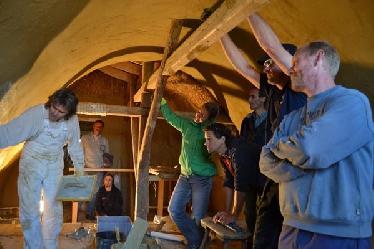 Toni Auer (Lehm Austria) bei der Lehmputz-Demonstration: Aufbringen des Glasfasergewebes und Glätten der letzten Schicht Feinputz.
