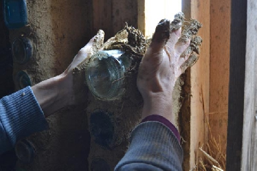 An der Giebelwand werden mit einer Mischung aus Lehm und Stroh (COB) Flaschen als kleine Lichtöffnungen in die Außenwand eingesetzt. Die Zwischenräume zwischen diesen