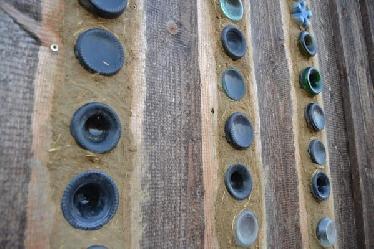 An der Außenseite (Fassade) werden die Flaschenböden zwischen der Holzschalung mit einer Lehm-Strohmischung (COB) möglichst luftdicht verputzt und darüber mit einem kleinen Dachvorsprung (Sims) vor Regen geschützt.