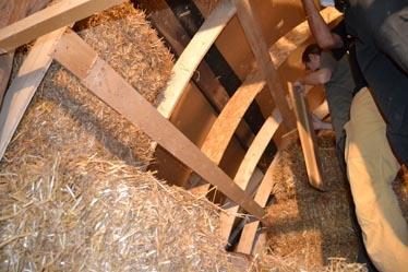 Einfüllen der Strohballen zwischen das Ständerwerk (Streben) wie beim Einfüllen in Holzständer- oder Rahmenkonstruktionen: sind die Ballen zu kurz, werden seitlich Ballenlagen dazu gefügt, bis die gewollte Dichte vorhanden ist.