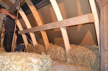 Im Fundamentbereich der Streben wurde die gesamte Tiefe bis zu den Unterdachplatten mit Strohballen befüllt. Dicke der Wand im Fußbereich: rund 1,2 m