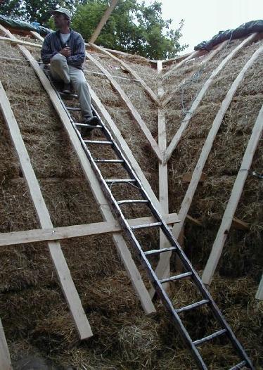 Raffinierte Dachkonstruktion: zwischen den Ballen werden Kanthölzer eingelegt, an denen die Dachsparren befestigt werden können. Auf diese Hilfskonstruktion wird quasi als Unterdachplatte Sperrholz montiert und eine regensichere Folie