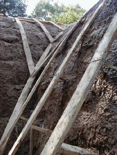 Die Strohballen werden vor dem Verplanken mit Lehm verputzt